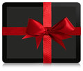 Tablet gift computer concept wrapped with a red ribbon and bow isolated on white with reflection at the bottom Royalty Free Stock Photos