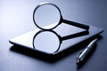 Tablet magnifying glass and pen still life shot of a mirrored on a switched off seven inches pc next to a Royalty Free Stock Image