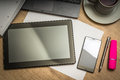 Tablet, mobile phone, pen, laptop and cup of coffee on table Royalty Free Stock Photo