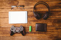 Tablet and music headphone next the joystick usb key and glasses on wooden table Royalty Free Stock Image