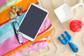 Tablet-pc on a beach towel with glasses and toys Royalty Free Stock Photo