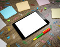 Tablet pc on the office table surrounded by multi colored paper clips and notebooks Royalty Free Stock Photos