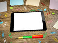 Tablet pc on the office table surrounded by multi colored paper clips and notebooks Royalty Free Stock Images