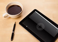 Tablet pc showing media player on screen with a cup of coffee on workplace and wooden work table close up Royalty Free Stock Photo