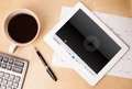 Tablet pc showing media player on screen with a cup of coffee on workplace and wooden work table close up Stock Image
