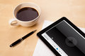 Tablet pc showing media player on screen with a cup of coffee on workplace and wooden work table close up Royalty Free Stock Images
