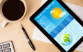 Tablet pc showing weather forecast on screen with a cup of coffe workplace and coffee wooden work table close up Royalty Free Stock Photos
