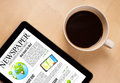 Tablet pc shows news on screen with a cup of coffee on a desk Royalty Free Stock Images