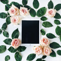 Tablet and pink rose flower with green leaves on white background