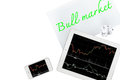 Tablet, smartphone and paper with text bull market is isolated o Royalty Free Stock Photo
