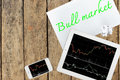 Tablet, smartphone and paper with text bull market on wood table Royalty Free Stock Photo