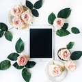 Tablet, vintage golden tray, retro plate and pink rose flower with green leaves on white background Royalty Free Stock Photo