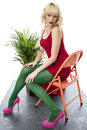 Tacones altos atractivos bochornosos de mini dress sitting chair pink del cortocircuito de la mujer joven Foto de archivo libre de regalías