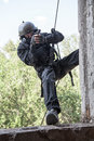 Tactical rappeling spec ops soldier in face mask during rope exercises with weapons Royalty Free Stock Photos