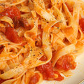 Tagliatelle pasta with tomato ragu and freshly ground pepper Stock Photo