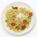 Tagliatelle with pesto and tomatoes from above ribbon pasta tossed a green basil grilled cherry garnished basil leaves topped Stock Photo