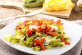 Tagliatelle with tomato mozzarella and bacon on complex background Stock Photography