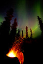 Taiga firepit camp fire sparks and northern lights open campfire burning hot in cast iron pit with spark trails flying off into Royalty Free Stock Images