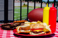 Tailgating meal with cheeseburger hot dog potato chips hamburger patties hot dog wieners mustard and ketchup bottles and american Stock Image