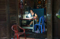 Tailor sewing clothing at home by sewing machine viet nam july people she sit in dark room work with lamp light old house have Royalty Free Stock Images