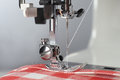Tailor sewing machine working part with linen fabric in the red cell Stock Photos