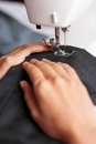 Tailor sews hands sewing a pair of trousers Stock Photos