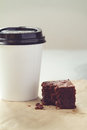 Take away coffee cup and chocolate brownie in muted tones crumbly Stock Photos
