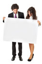 Take a look at this offer an elegant business couple holding blank whiteboard and promoting something Stock Photos