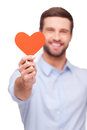Take my heart handsome young man stretching out shaped valentine card and smiling while standing against white background Royalty Free Stock Photos