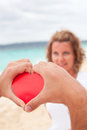 Take my heart love concept loving couple on beach red in hand Royalty Free Stock Photo