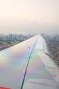 Take off view of plane s wing from inside window cabin while the plane on or ready to land with city view from above Royalty Free Stock Images