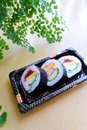 Take out sushi snack platter a photograph showing some delicious pieces on a away box packed for snacks to go ingredients include Royalty Free Stock Image