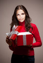 Take a peek portrait of an attarctive young brunette woman opening red christmas gift box in mysterious lighting Royalty Free Stock Images