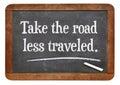 Take the road less traveled motivational advice on a vintage slate blackboard Stock Photo