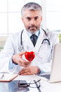 Taking care of your heart mature grey hair doctor holding shape toy and looking at camera while sitting at his working place Stock Photos