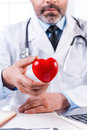 Taking care of your heart mature grey hair doctor holding shape toy and looking at camera while sitting at his working place Stock Images
