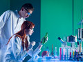 Taking fingerprints side view of two forensics scientists from bottle in a laboratory Stock Photo