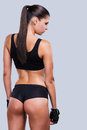 Taking good care of her body rear view beautiful young sporty woman with perfect standing against grey background Stock Photo