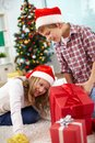 Taking a look inside giftbox portrait of happy siblings looking big red on christmas evening Stock Photo