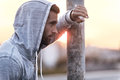 Taking a minute break side view of thoughtful young man wearing hood and looking away while standing outdoors Royalty Free Stock Photos