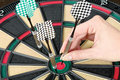 Taking out dart from dartboard female hand one on Stock Photography
