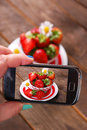 Taking photo of fresh strawberries by smartphone hand holding and in bowl on wooden rustic table Stock Images
