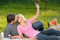 Taking photographs of themselves loving young couple taking the on summer picnic Royalty Free Stock Images