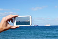 Taking a picture with mobile phone man pictures of the sea Royalty Free Stock Photo
