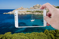 Taking a picture with smartphone in sardinia the wonderful colors of the sea cala spinosa bay of capo testa gallura photographed Royalty Free Stock Photography