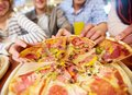 Taking pizza image of teenage friends hands slices of Stock Images