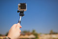Taking selfie hand with photo camera on monopod Royalty Free Stock Photos