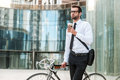 Taking time to enjoy this morning thoughtful young businessman holding cup of coffee and looking away while leaning at his bicycle Stock Images