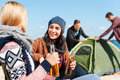 Taking time to have a rest two beautiful young women talking each other and smiling while holding bottles with beer with two men Stock Images
