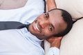 Taking time to for a minute break top view of handsome young african man in shirt and tie holding hands behind head and smiling Stock Images